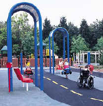 photo of a play area with protective shelters and benches offset from the boundary of the accessible route