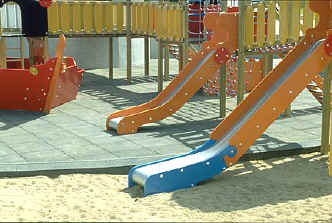photo of 2 slides with one connected by an accessible route and the other by inaccessible surfacing (sand)
