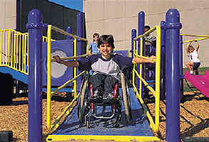 photo of boy using a wheelchair descending ramp with handrails on both sides