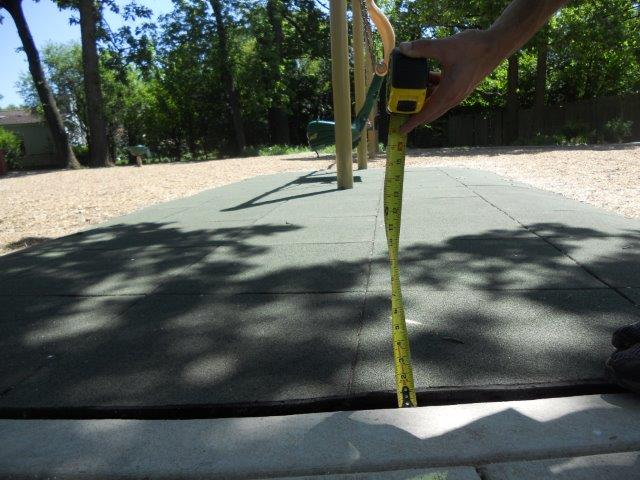 The change in level from the concrete path to the tile surface is measured with a tape measure.