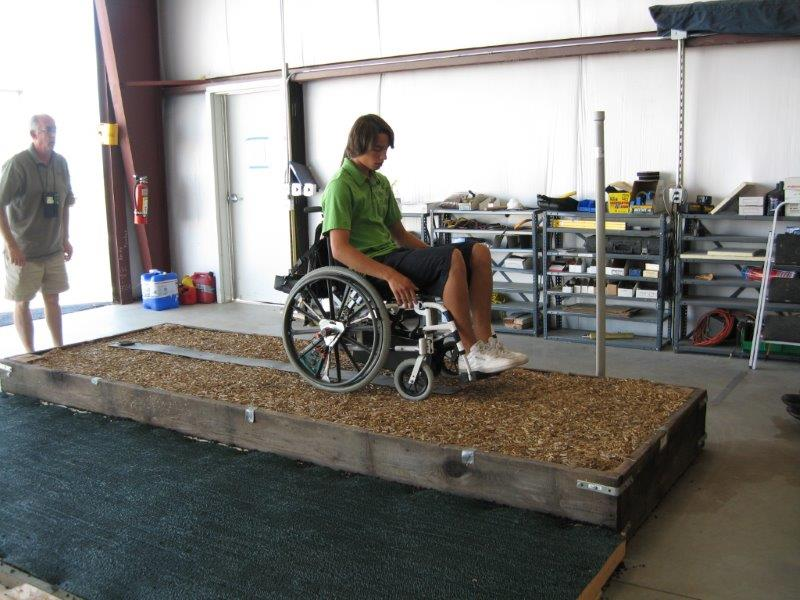 A man in using a manual wheelchair wheels across a sample surface plot in the laboratory.