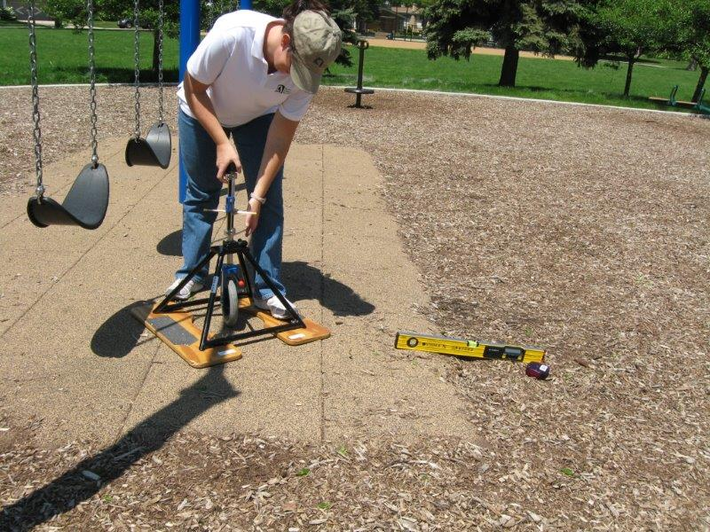 A researcher uses a rotational penetrometer on a playground surface of tiles and engineered wood fiber.