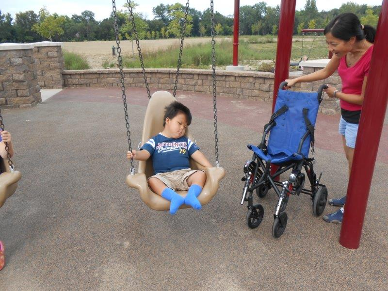 A mom sets a wheelchair adjacent to the swing in preparation to assist her young son in transfer from the swing to his wheelchair.