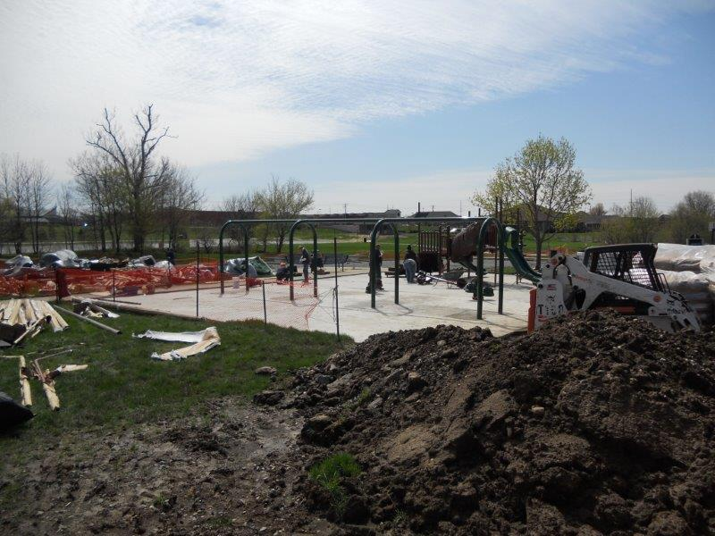 A mound of excavated dirt is shown in the foreground while the new playground construction site is prepared for installation of the surface system.