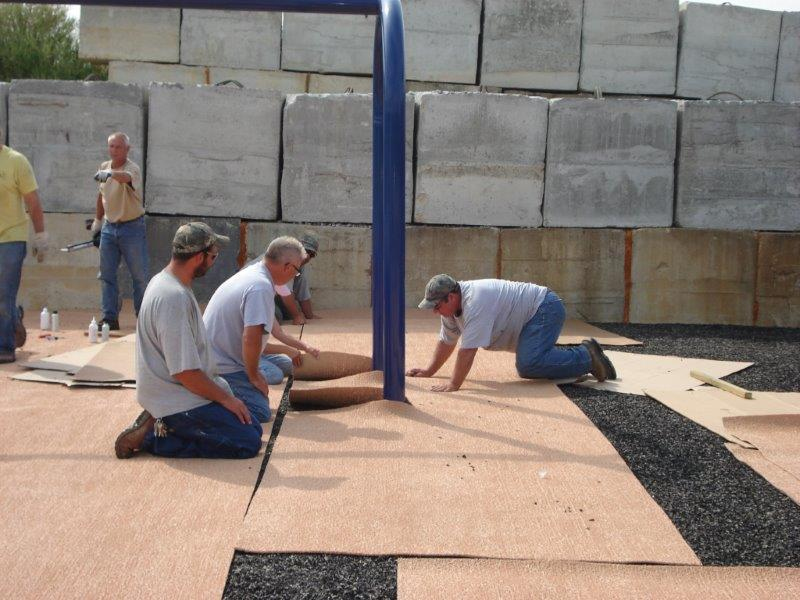 A park maintenance crew of four men are shown on their knees seaming together the top mat of a hybrid surface system as it is installed.