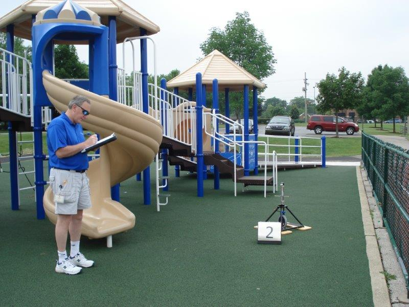 A playground owner records the findings after installation of the new poured-in-place rubber surface.
