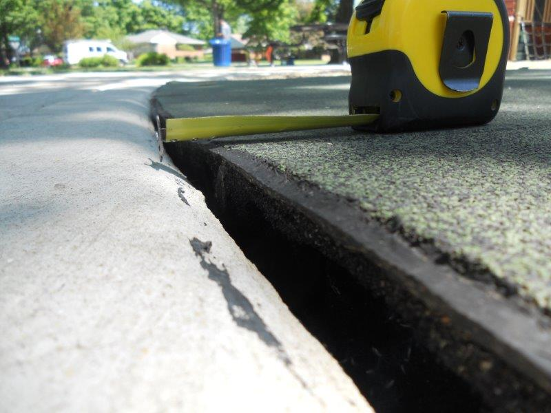 A close-up of a gap between the concrete and rubber surface is shown with a tape measure.