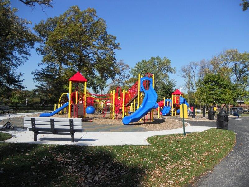 A composite play structure surfaced with poured in place rubber and engineered wood fiber.