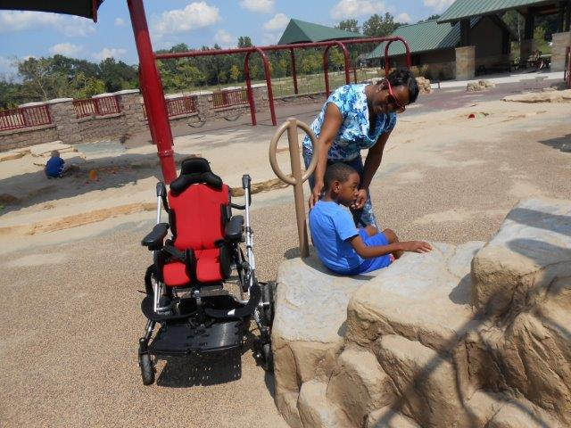 A mom assists her young son to move from his wheelchair to seated on the climbing rock-like transfer system.
