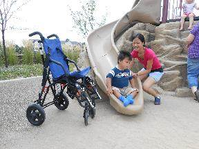 A little boy comes down the slide as he is assisted by his mom.  A wheelchair is seated next to the bottom of the slide.