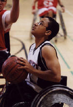 boy in wheelchair shooting basketball on court