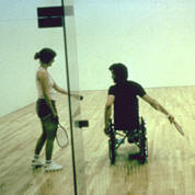 photo of man in wheelchair playing indoor racket ball
